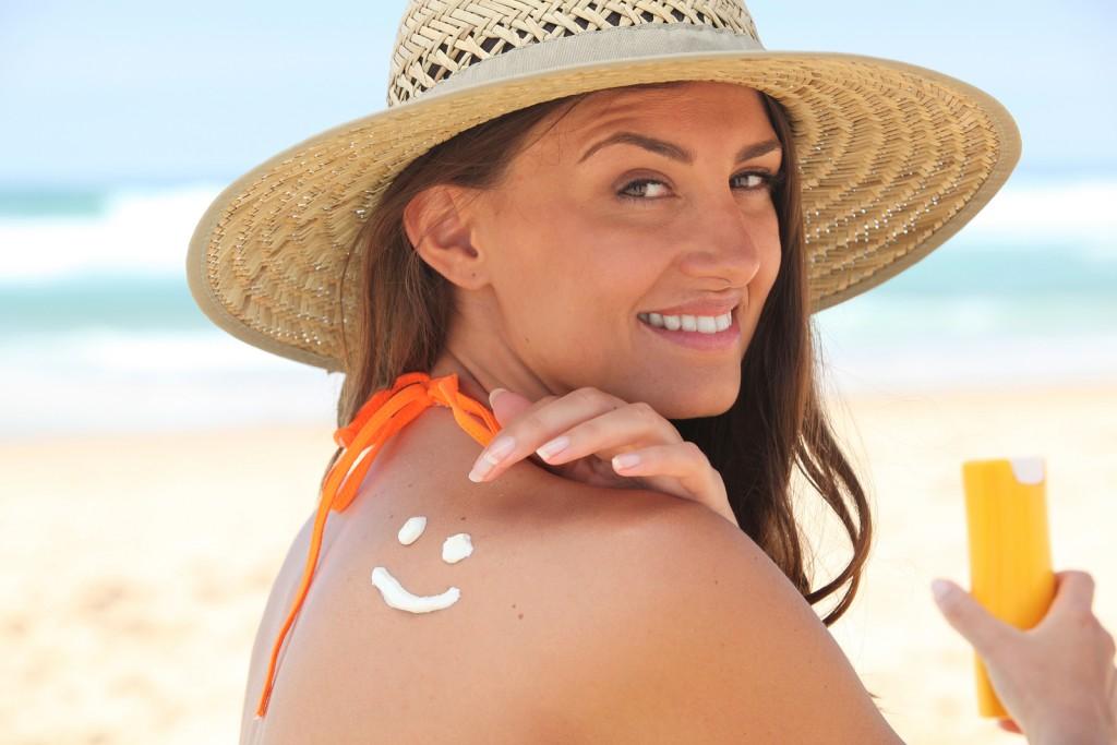 Woman applying suncream at the beach